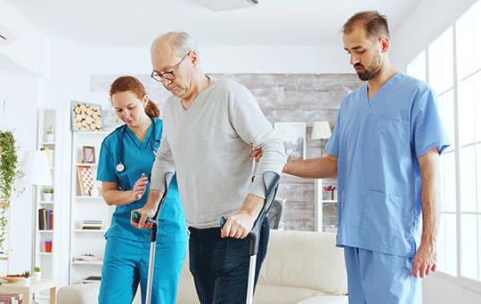 Pflegerin und Pflegehelfer unterstützen Mann beim Gehen mit Gehilfen