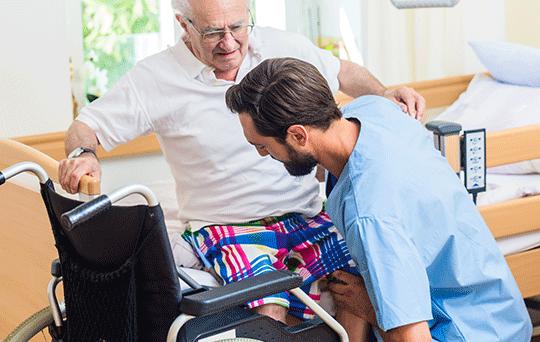 Pfleger Hilf Mann in seinen Rollstuhl